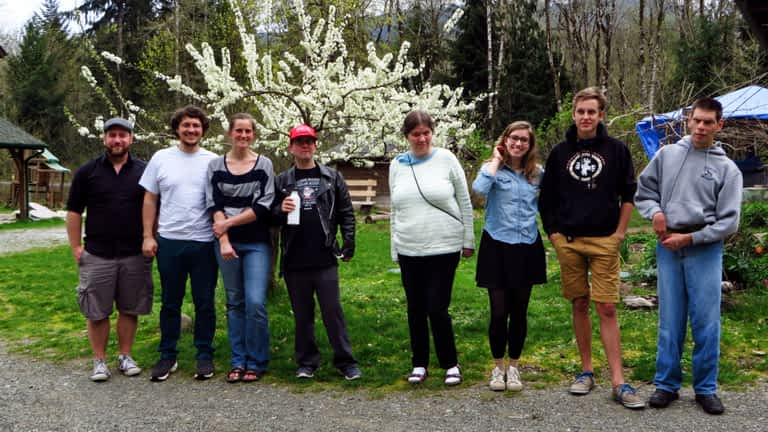 A group of people ranging from their teens to middle-aged pose together in front of a small tree with white flowers.