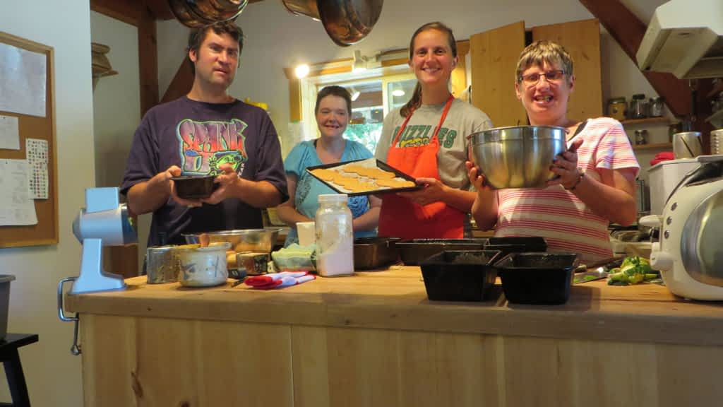 Three women and one man are baking in a kitchen.