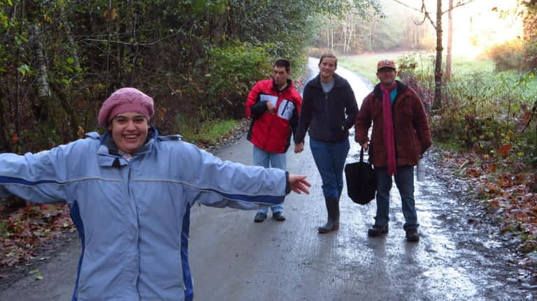Four people are walking on a road in the middle of a forest. One young lady is in front of the group with her arms spread wide, laughing. The other three are holding hands behind her.