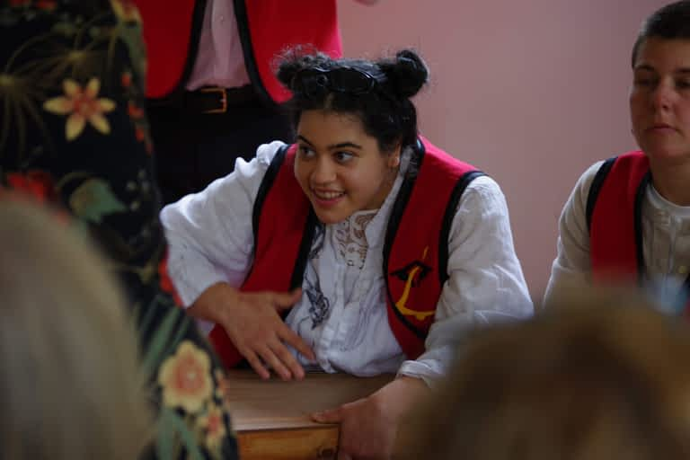 A young woman plays a stringed instrument on her lap. She is wearing a white shirt and a red vest.
