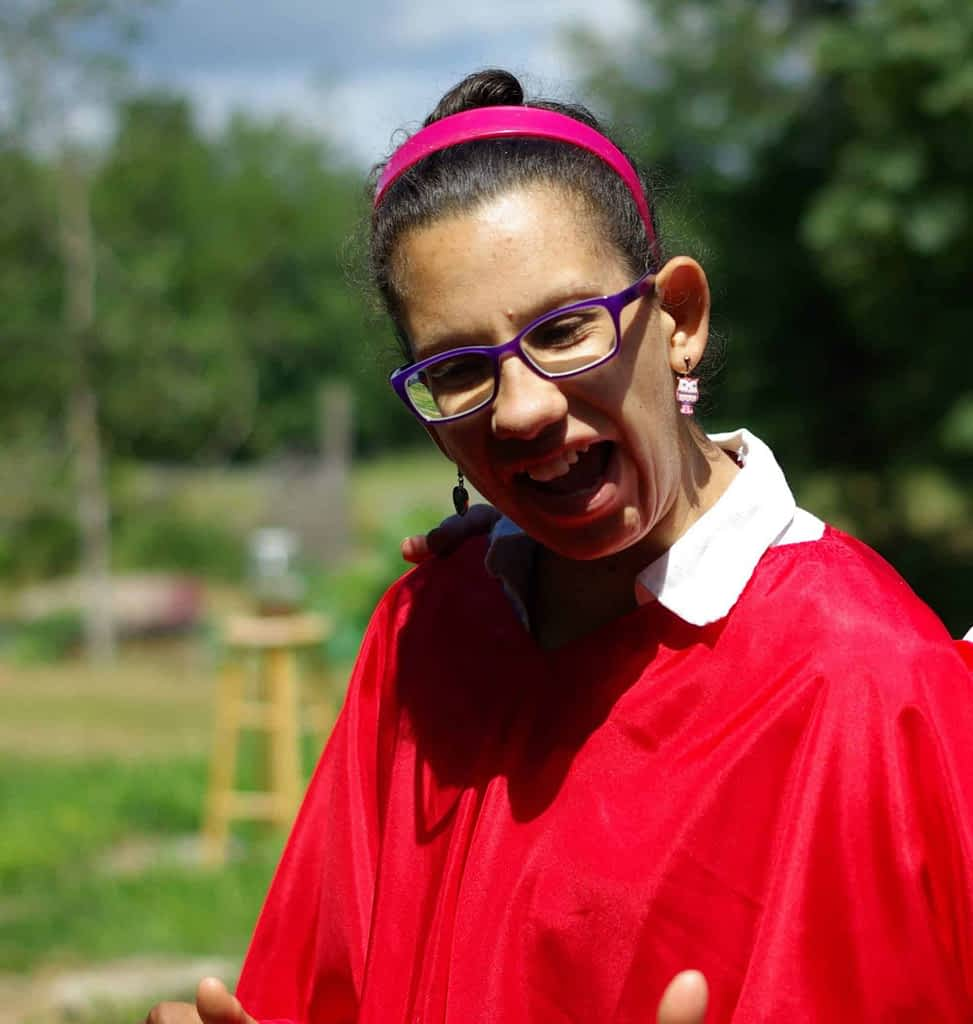 A young woman laughs. She is wearing a bright red shirt and glasses.